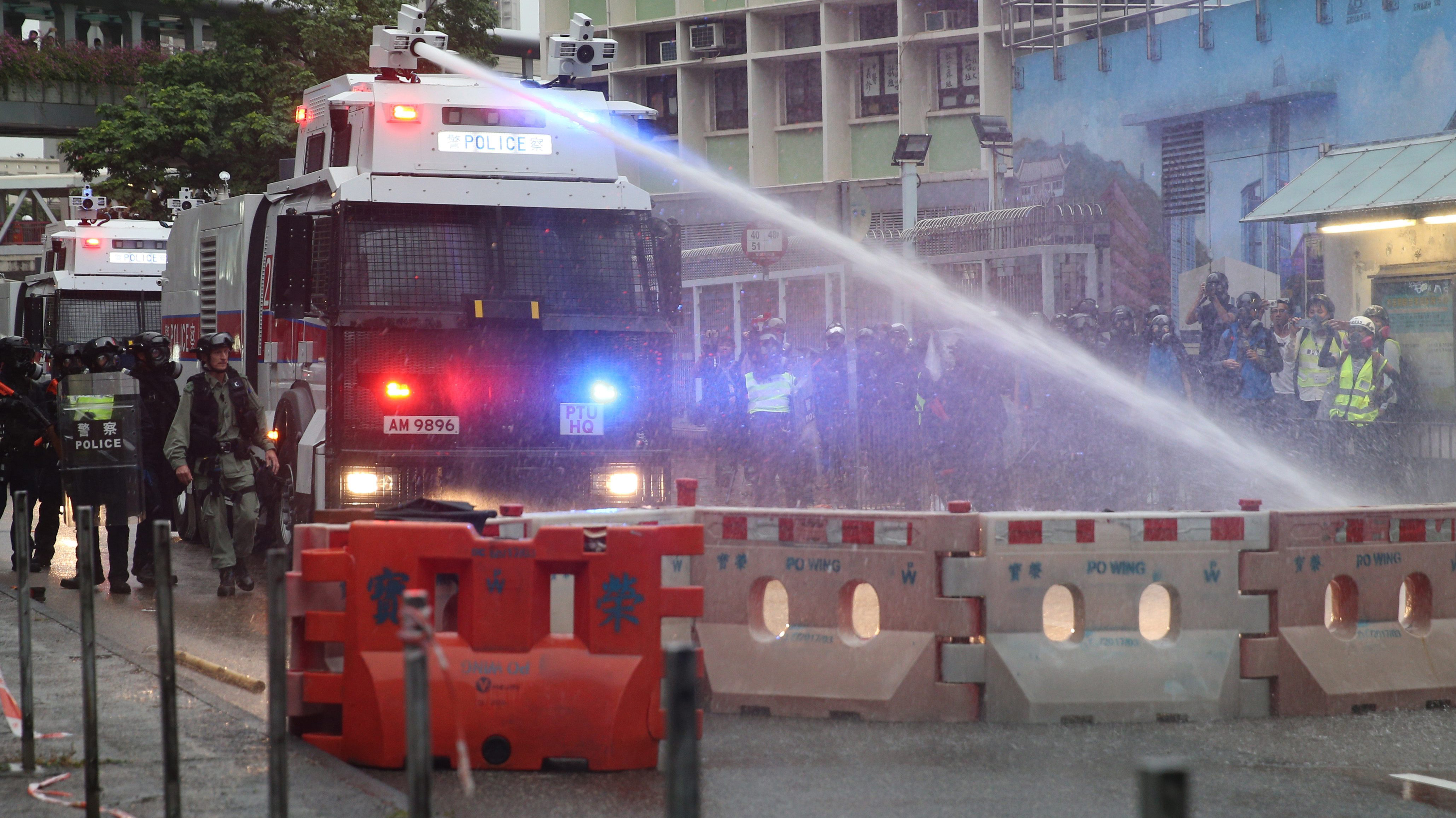 Police draw guns, use water cannons on Hong Kong protesters